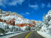 Snow covered red rocks lead travelers into Sedona from Oak Creek Canyon